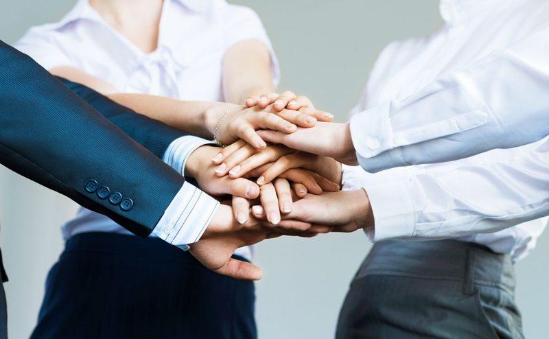 Tres-empleados-juntando-sus-manos