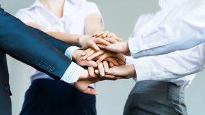 Humildad, tres empleados juntando sus manos