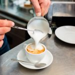 37779263 - barista in cafe or coffee bar preparing proper cappuccino pouring milk froth in a cup