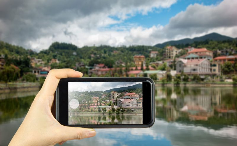 51728318 - taking photo on smart phone. building along lake in sapa city, lao cai, vietnam