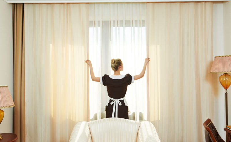 46546639 - hotel service. female housekeeping chambermaid worker with opening curtains of window in room