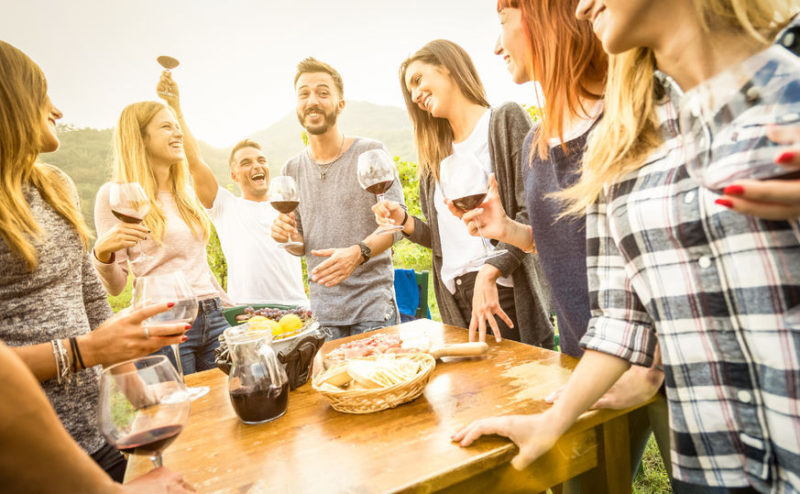 66621079 - young friends having fun outdoor drinking red wine - happy people enjoying harvest time at farmhouse vineyard winery - youth friendship concept with focus on guy toasting in middle frame - warm filter