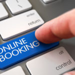 Online Booking - Modern Keyboard Button. White Keyboard with Online Booking Blue Button. Man Finger Pushing Online Booking Blue Key on Metallic Keyboard. 3D Render.