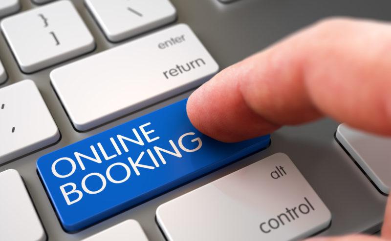Online Booking - Modern Keyboard Button. White Keyboard with Online Booking Blue Button. Man Finger Pushing Online Booking Blue Key on Metallic Keyboard. 3D Render.