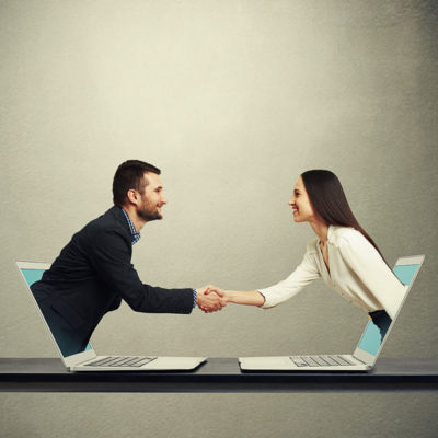 39302600 - smiley businessman and businesswoman come out from laptop, shaking hands and looking at each other over dark grey background